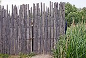 istock old gray wooden gate of long boards in the green grass 1049721058