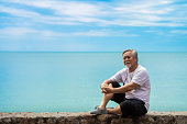 old gray-haired Asian man wearing casual clothes, enjoying the view of the sea and sky background.