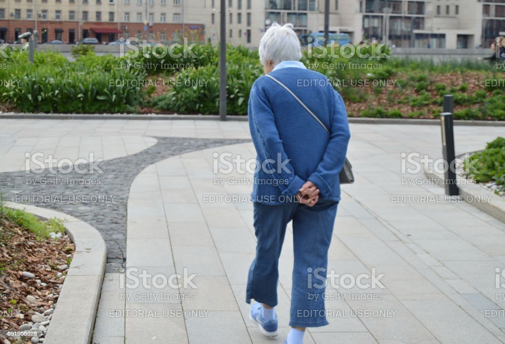 Old gray-haired, elderly woman walking in Muzeon Park in Moscow, may 2017 stock photo