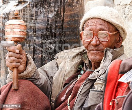 Lamayuru, India - June 17, 2012: Old gray-haired ladakhi man with glasses and hand prayer wheel in traditional clothes and knitted hat attentively