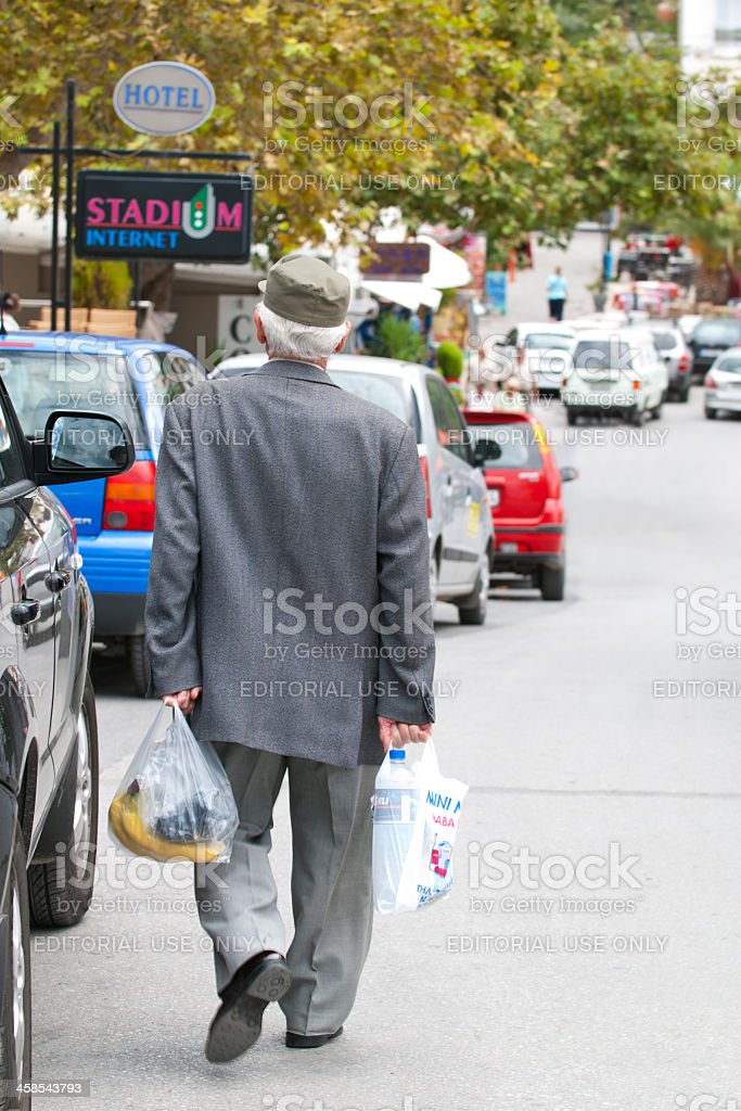 Old Greek senior brings his purchases home royalty-free stock photo