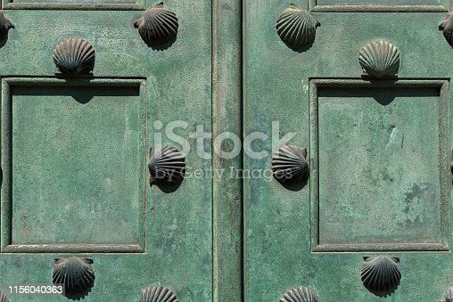 Old green wood door with scallop shell studs close up