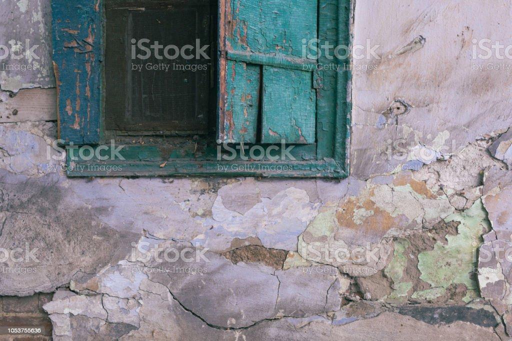 Antiga janela aberta verde em pó e sujeira. Parede arruinada com manchas e fissuras - foto de acervo