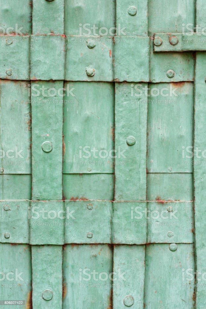 Old green painted riveted metal door detail stock photo