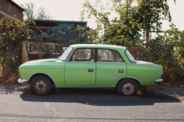 old green sedan car parked near home garden - auto a combustibile alternativo foto e immagini stock