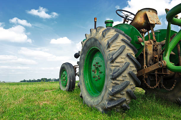 Old green tractor in the field stock photo