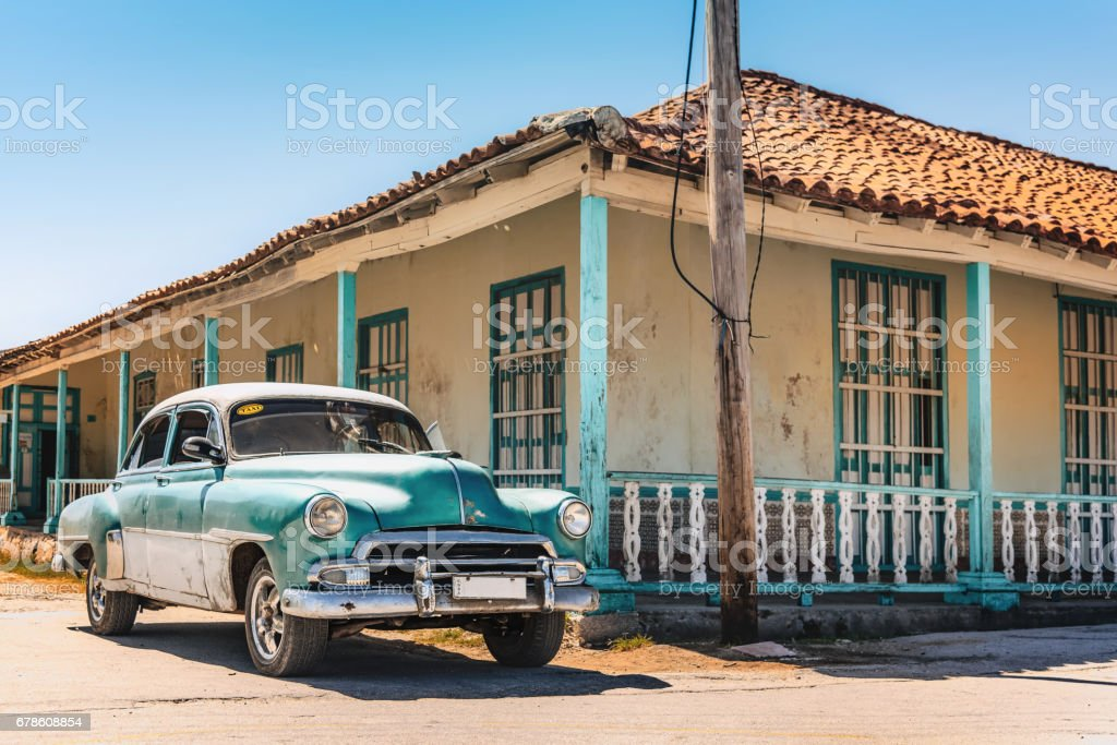 old green vintage taxi car in sunny Gibara in Cuba stock photo