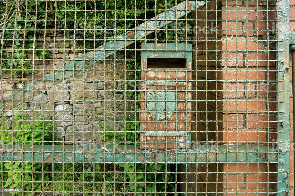 Old green wire gate with a letterbox stock photo