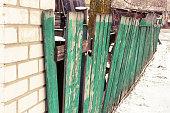istock Old green wooden broken fence 1057474778