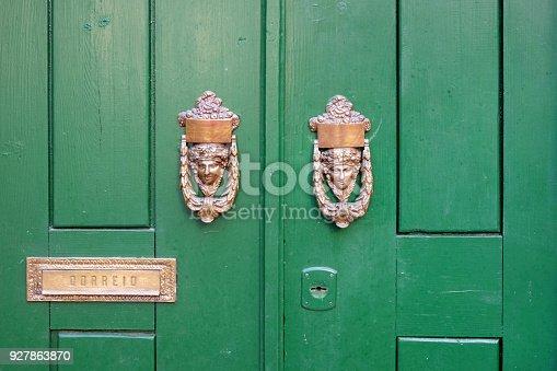 istock Old green wooden doors with bronze handles. 927863870