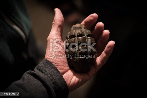 istock Old grenade held in hand's open palm 629987912
