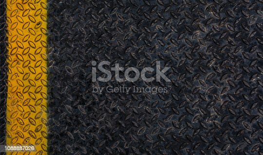istock Old grunge and rusty black iron plate of steel floor with yellow line seamless background and texture. 1088887026