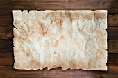 istock Old grunge paper template for announcement on wood texture 1183785204
