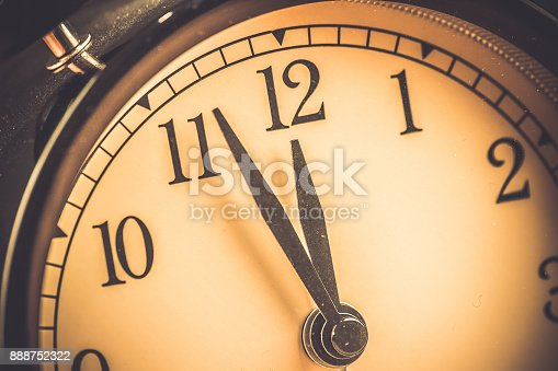 istock old grunge vintage alarm clock is showing midday or midnight movement. It is twelve o'clock, holiday happy new year festive and christmas or lunch 888752322