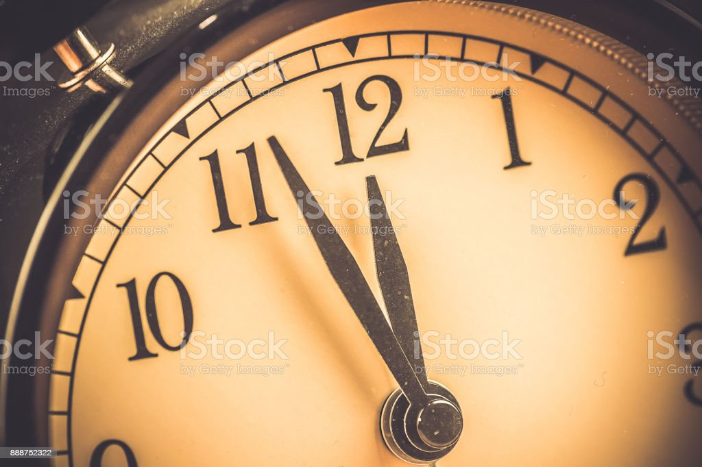 old grunge vintage alarm clock is showing midday or midnight movement. It is twelve o'clock, holiday happy new year festive and christmas or lunch stock photo