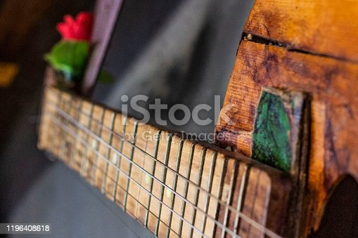 1014432572 istock photo old guitar on concrete wall background with blurred front and back background with bokeh effect 1196408618