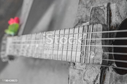 1014432572 istock photo old guitar on concrete wall background with blurred front and back background with bokeh effect 1196408620