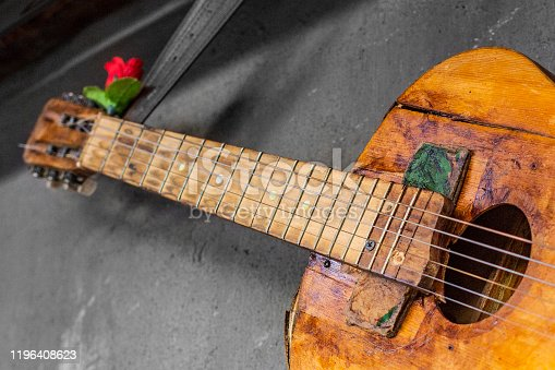 1014432572 istock photo old guitar on concrete wall background with blurred front and back background with bokeh effect 1196408623