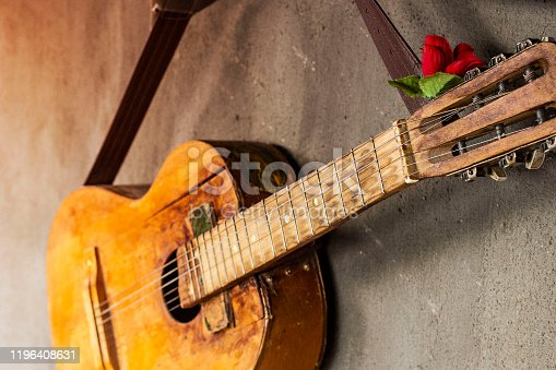 1014432572 istock photo old guitar on concrete wall background with blurred front and back background with bokeh effect 1196408631
