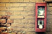 Old gumball machine on ragged brick wall