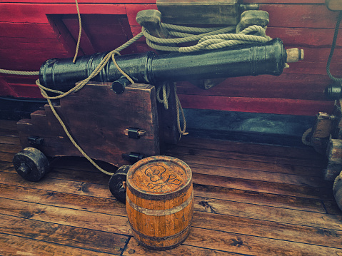 Old gun and powder keg on the deck of a wooden sailing ship
