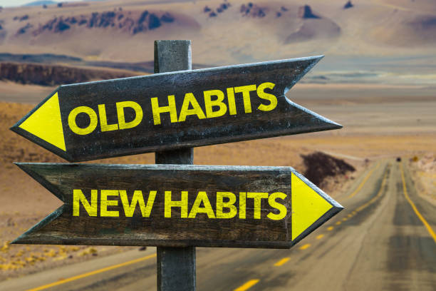 Old Habits - New Habits signpost Old Habits - New Habits signpost in a desert road background routine stock pictures, royalty-free photos & images