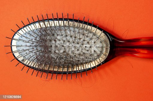 istock Old hairbrush with hair on an orange background close-up, top view 1210826594