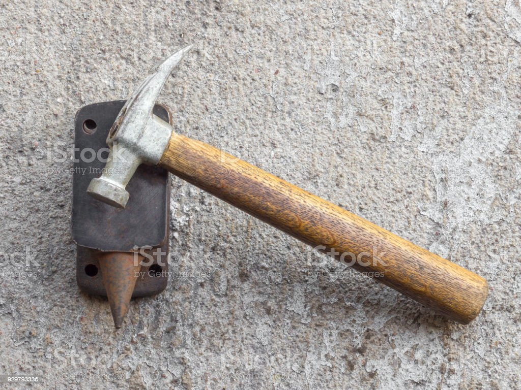 Old hammer and miniature rusty anvil with concrete background stock photo