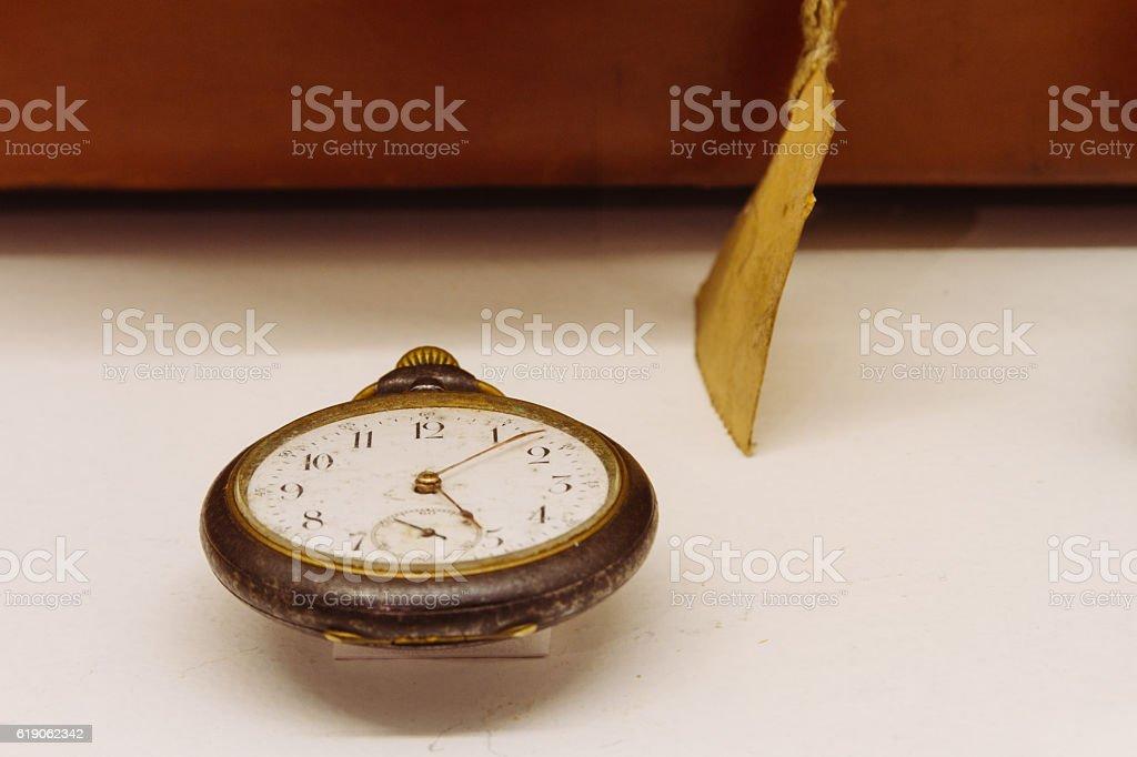 Old hand clock next to an antique suitcase - foto de acervo