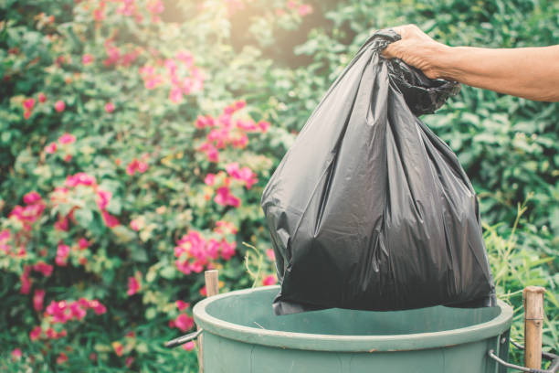Old hand holding plastic bag in to trash stock photo