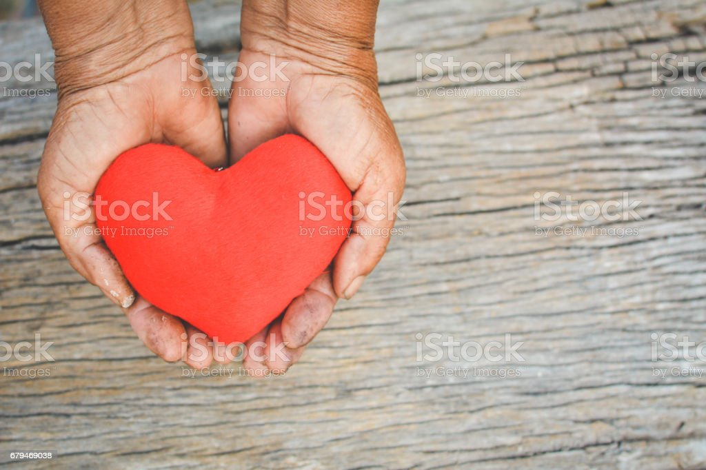 Old hand holding red heart shape vintage tone royalty-free stock photo