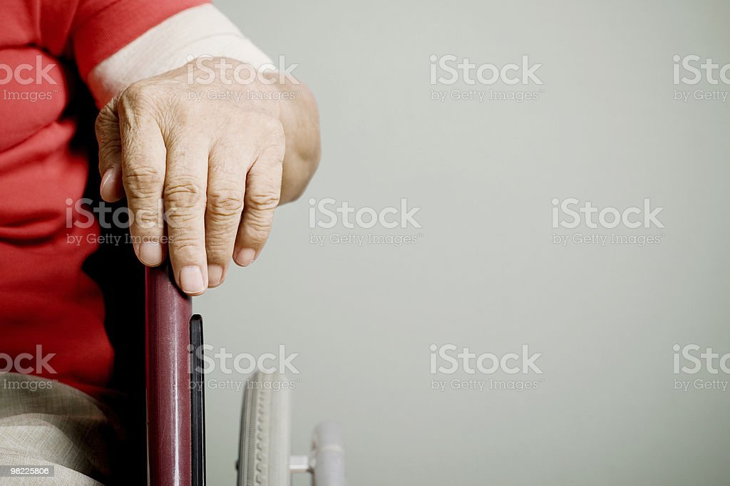 Old hand on wheelchair royalty-free stock photo