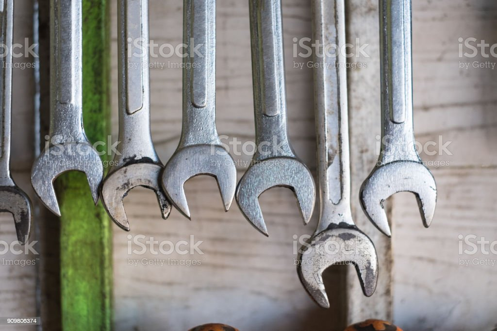 Old hand tools hanging on wall in workshop or auto service garage,...