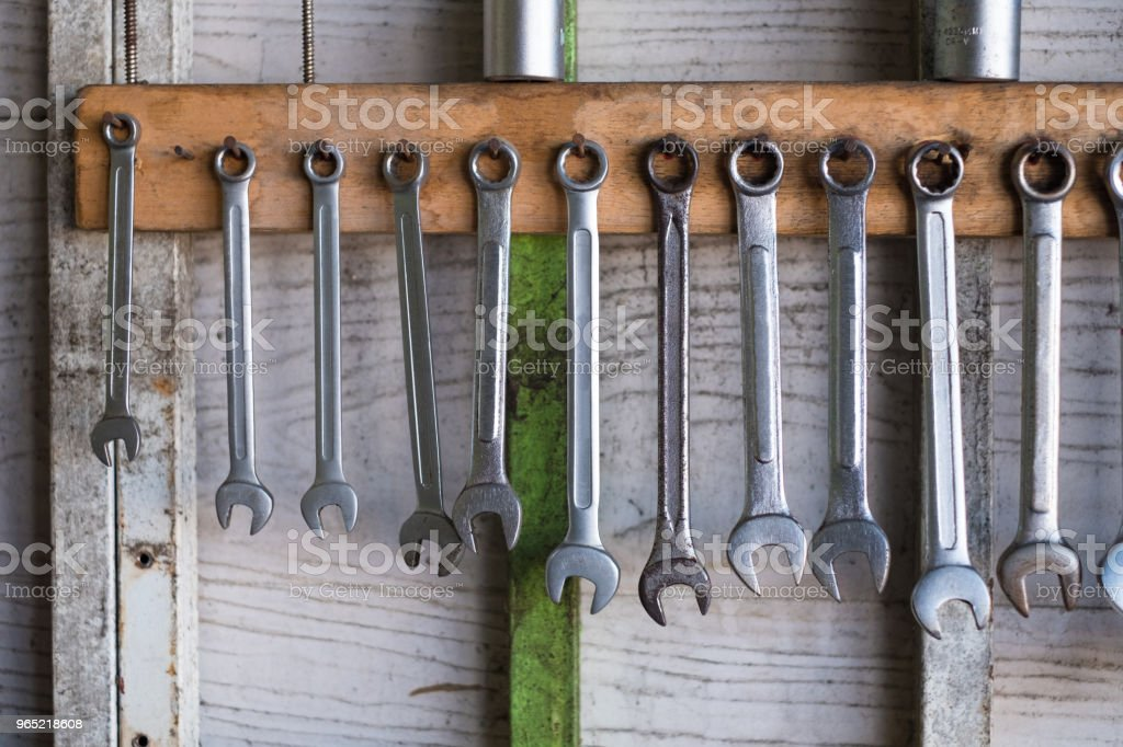 Old hand tools hanging on wall in workshop or auto service garage, many tool shelf against a wall, car mechanic concept. zbiór zdjęć royalty-free