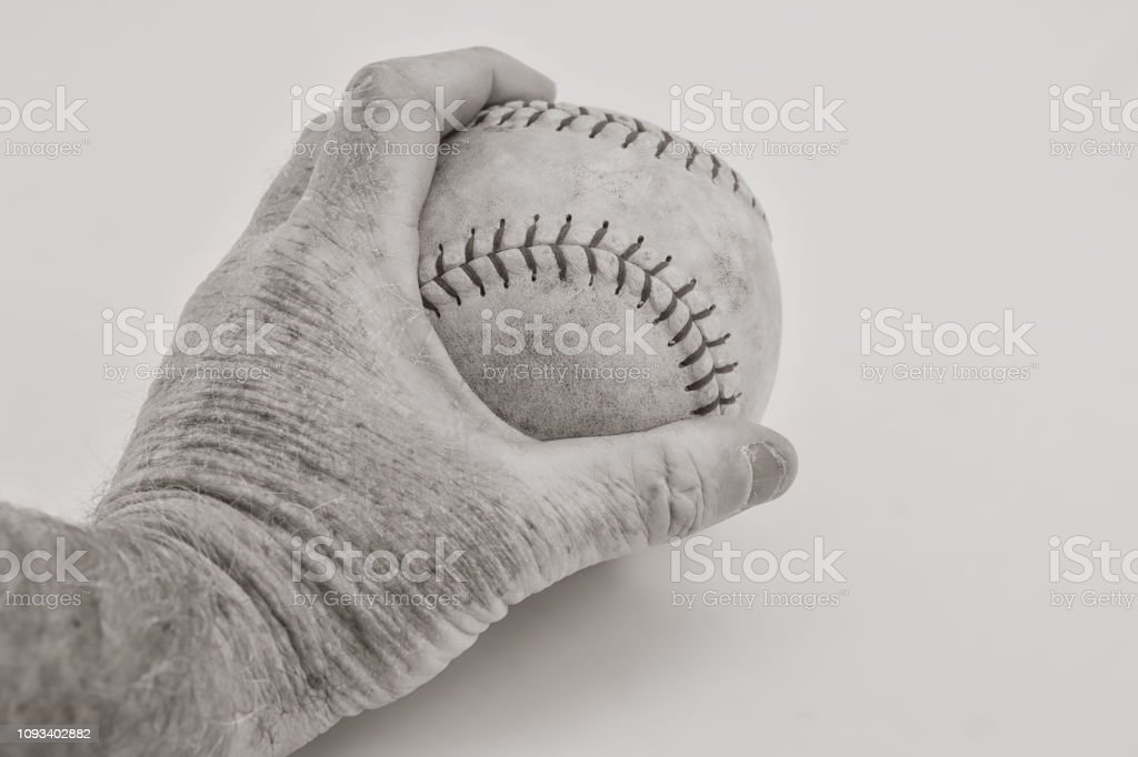 Isolated softball in older male hand on white background with room...