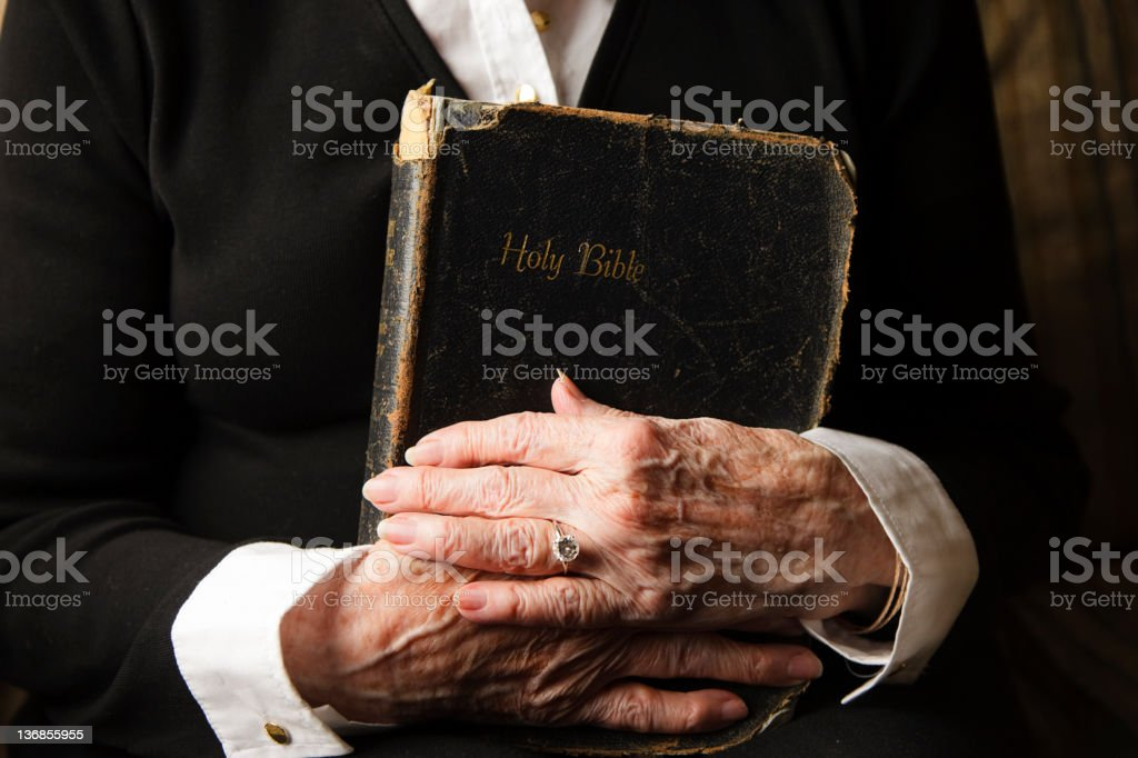 Old Hands on an Antique Bible stock photo