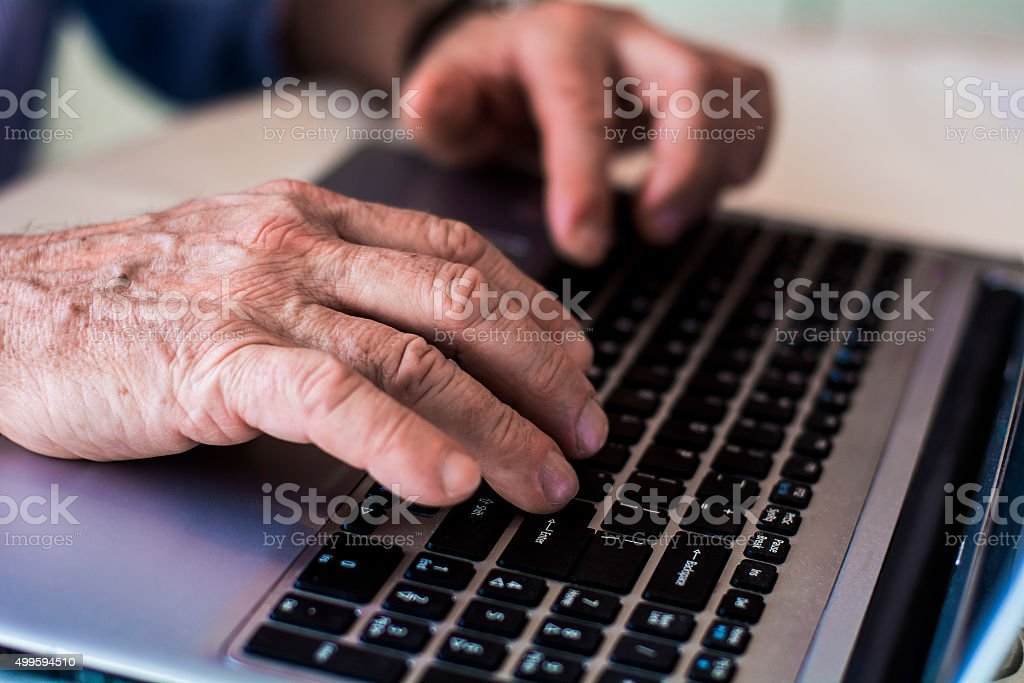 Old hands on the keyboard stock photo