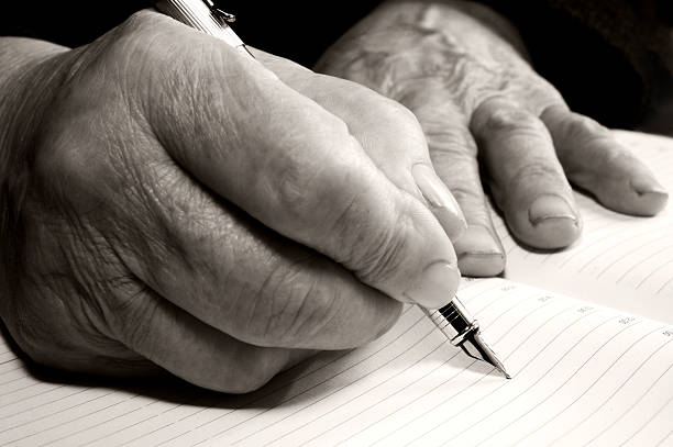 Old hands with a pen stock photo
