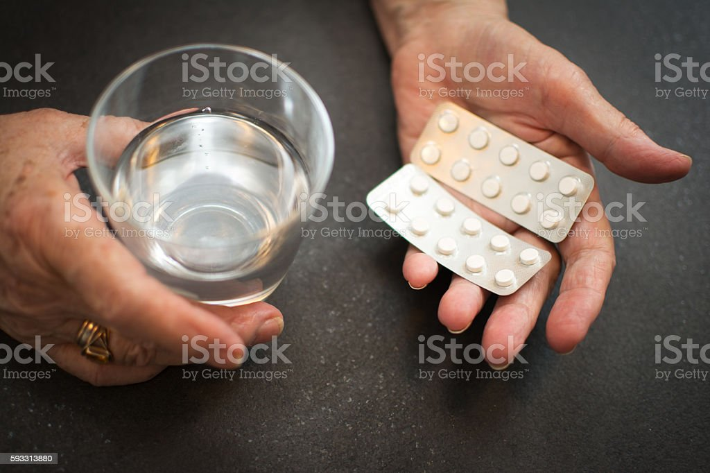 Old hands with tablets and a glass of water. – Foto