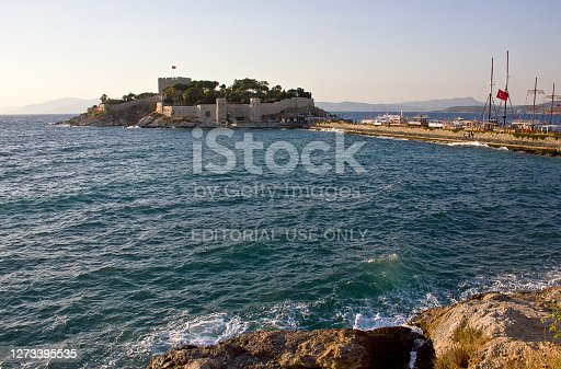 Aydın, Turkey - July 15, 2020: People visit the old harbor on Pigeon Island (güvercin ada) that Kusadasi castle in Turkey. It was built in Byzantine Era, now the castle houses the museum and is the lovely place for many tourists. There is a statue of Barbaros Hayrettin Paşa who is ottoman sailor.