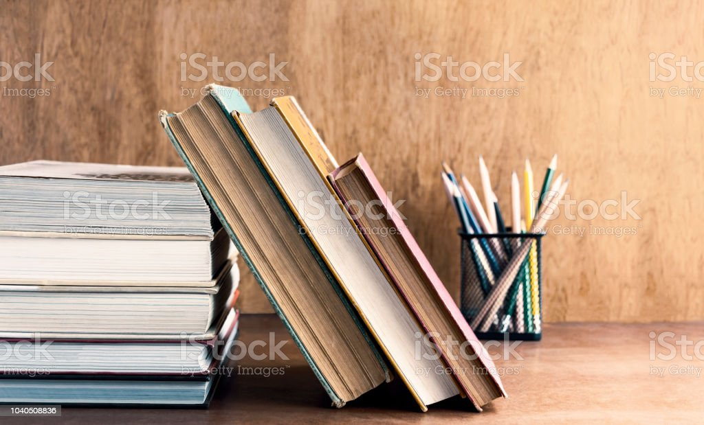 Old hardback and textbook stacked on the wooden table. The concept of...