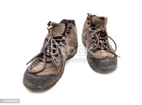 A pair of used hiking boots isolated on a white background.