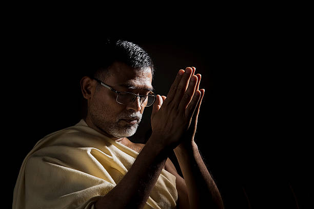 old hindu man praying with folded hands - hinduism stock photos and pictures