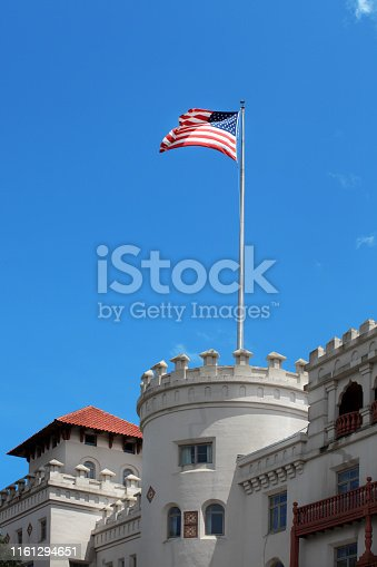 Close up old historic building detail with flagpole and waving American flag over sunny blue sky in downtown of St Augustine, Florida, USA