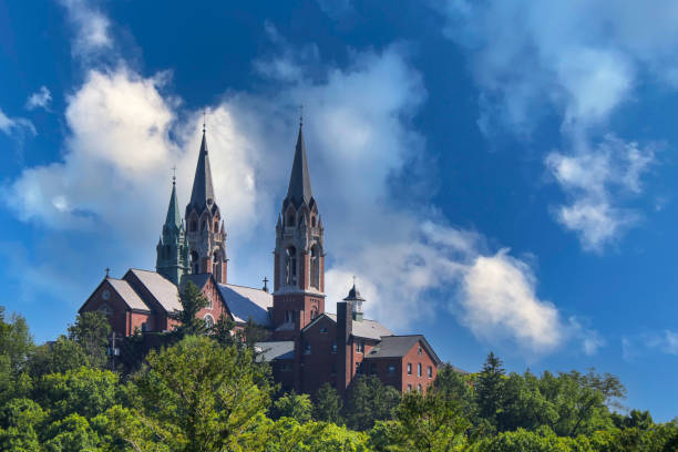 old historic church with twin steeples on a high hill mountain with dramatic sky shot from a distance as a landscape scene stock photo