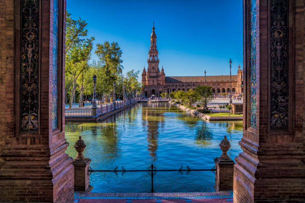 Old Historical Buildings In The Plaza De Espana In Seville Spain Seville, Spain - April 4, 2017: Looking Through Architectural Pillars At The View Of The Pond And Old Buildings Within The Plaza De Espana cordoba spain stock pictures, royalty-free photos & images