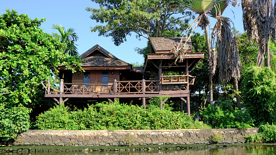 old-home-made-of-teak-wood-along-a-thai-klong-in-bangkok-city-picture-id1147542869