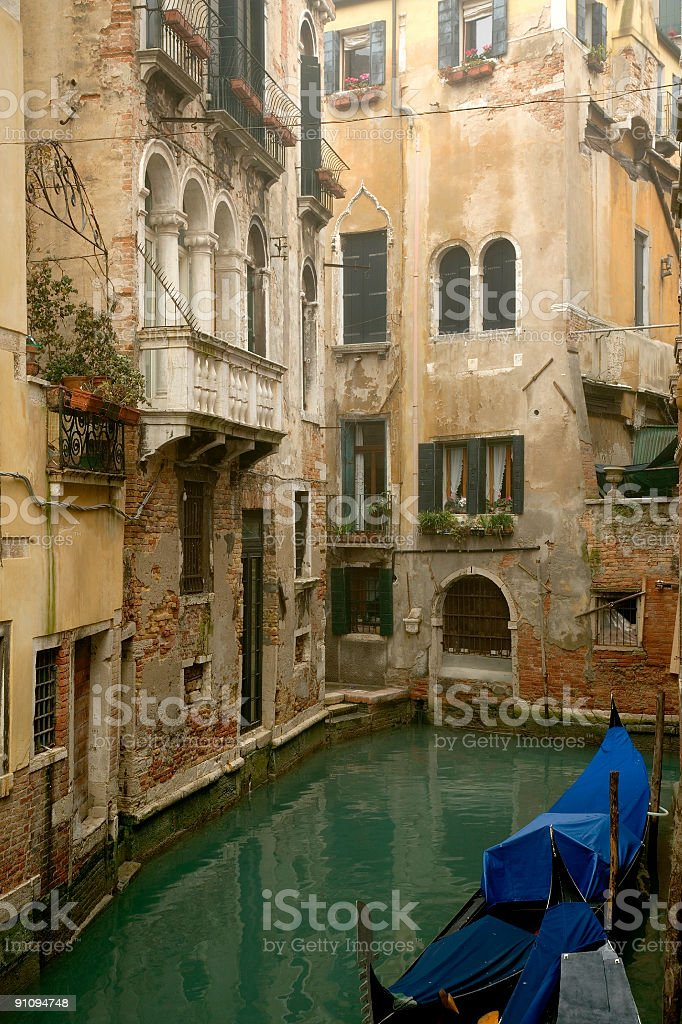 Old homes and small canal with gondola in Venice royalty-free stock photo