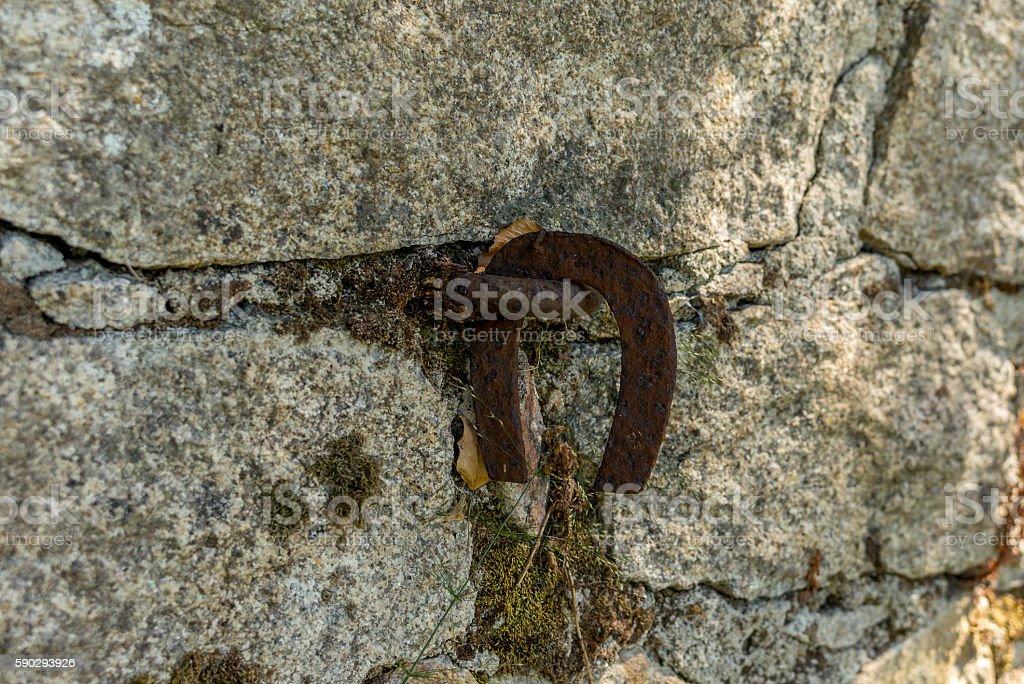 Old horse shoe hanging in a stone wall - 2 Стоковые фото Стоковая фотография