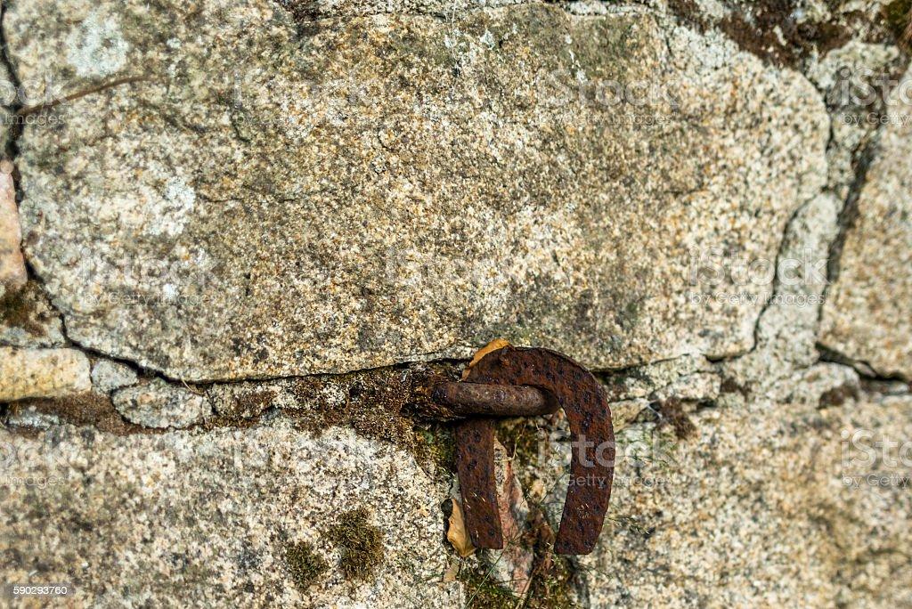 Old horse shoe hanging in a stone wall royaltyfri bildbanksbilder